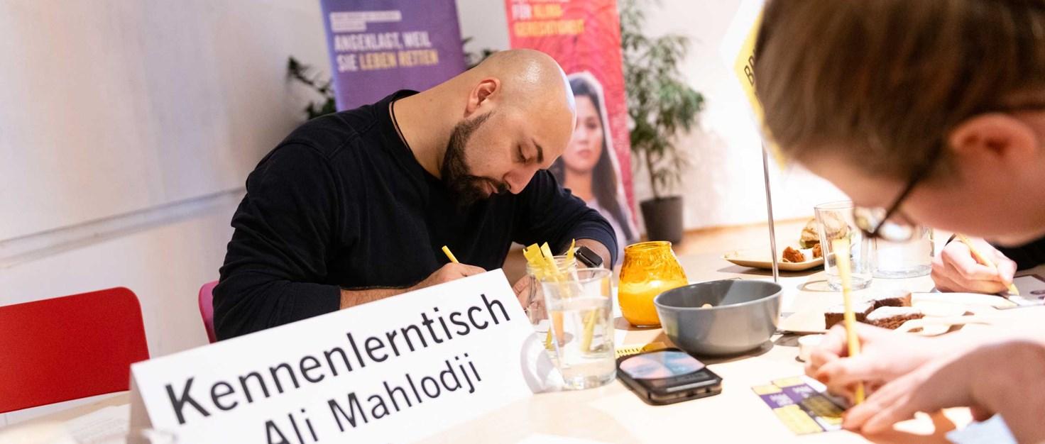 Ali-Mahlodji-schreibt-mit-beim-Briefmarathon Liebentritt Christoph 10.-Dezember-2019 | © Christoph Liebentritt/Amnesty International
